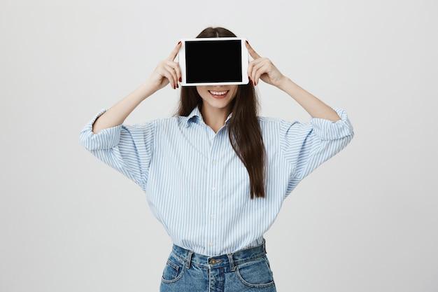 Dumme frau, die zunge zeigt und augen mit digitalem tablett bedeckt
