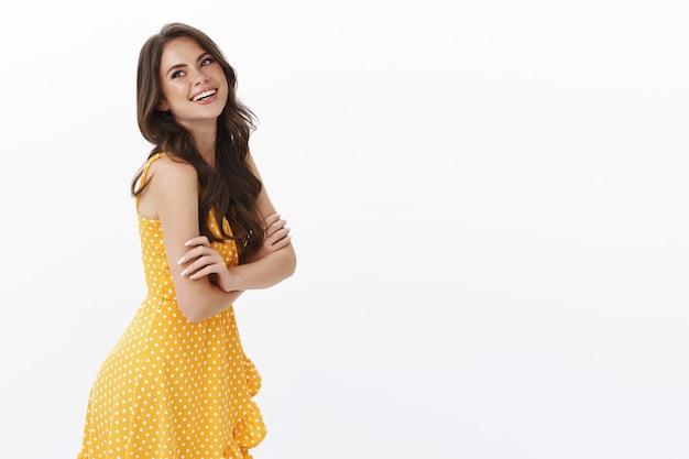 Dumme, fröhliche, wunderschöne brünette kaukasierin, gelbes sommerkleid tragen, erfreut und fröhlich lachen, standprofil nach hinten schauen, linken kopienraum zufrieden, frohes schönes wetter