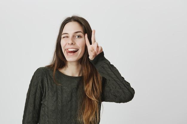 Dumme glückliche frau mit langen haaren tun friedenszeichen, zwinkert und zeigt zunge, lächelt fröhlich