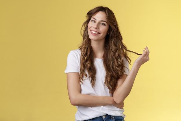 Dumme süße feminine sinnliche lockige frau kippt den kopf, der die haarsträhne rollt, die locke lächelt, erfreut, interessiert zuhört, kokette konversation, kokett anstarrend, kameraständer gelber hintergrund