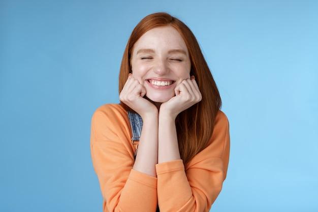 Dumme süße glückliche rothaarige freundin, die breit lächelt, schließen die augen verträumt zusammengedrückte wangen erfreut gefragter date-typ steht gerne auf blauem hintergrund und freut sich, hat einen fantastischen glücklichen tag, der triumphiert