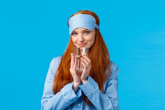 Dumme und flirty, weibliche rothaarige frau in niedlicher nachtwäsche und schlafmaske, kokett aussehend mit erfreutem zartem lächeln, trinkwasser, tag gesund und aktiv beginnen, stehende blaue wand