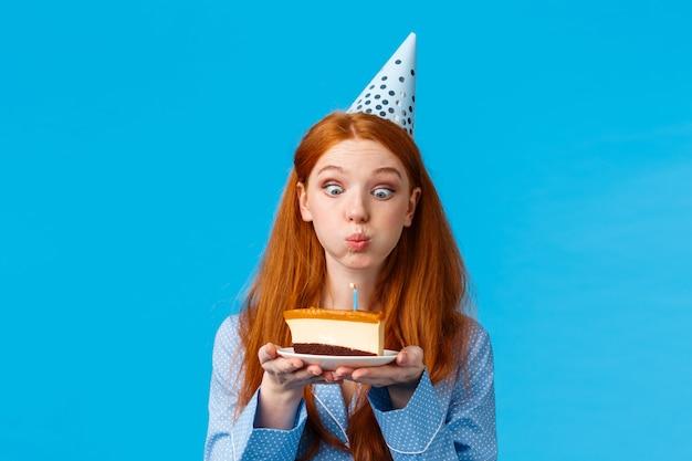 Dumme und niedliche glamour-rotschopf-kaukasierin in b-day-mütze und nachtwäsche, hält scheibenkuchen mit kerze, bläst aus und wünscht sich mit lustigem ausdruck, stehende blaue wand