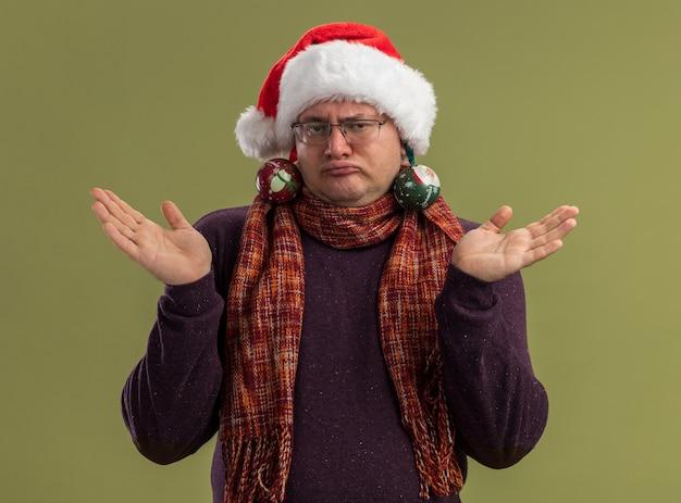 Dummer erwachsener mann mit brille und weihnachtsmütze mit schal um den hals, der leere hände mit weihnachtskugeln zeigt, die an seinen ohren hängen, isoliert auf olivgrüner wand