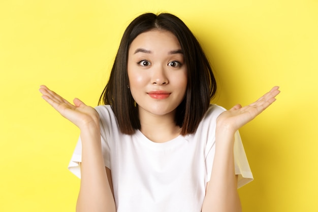 Dummer fehler. nahaufnahme eines süßen asiatischen mädchens, das sich entschuldigt, die schultern zuckt und mit oops-gesichtsausdruck lächelt und über gelbem hintergrund steht