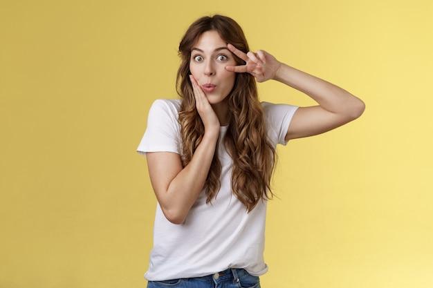 Dummes koquestrisch gutaussehendes kaukasisches mädchen lockige frisur faltende lippen amüsiert interessiert berühren wange weiblich sinnliche pose zeigen sieg friedenszeichen optimistischer stand fasziniert gelber hintergrund