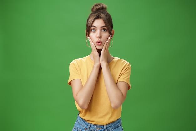 Dummes süßes und zartes junges weibliches modell mit sauberer haut, die lippen faltet, hände zu wangen drückend