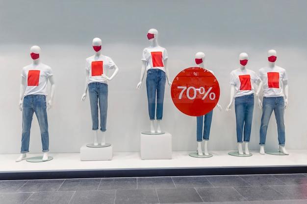 Dummies in masken mit t-shirts mocap und stand kündigen rabatte während des verkaufszeitraums in der mall an. coronavirus pandemie.
