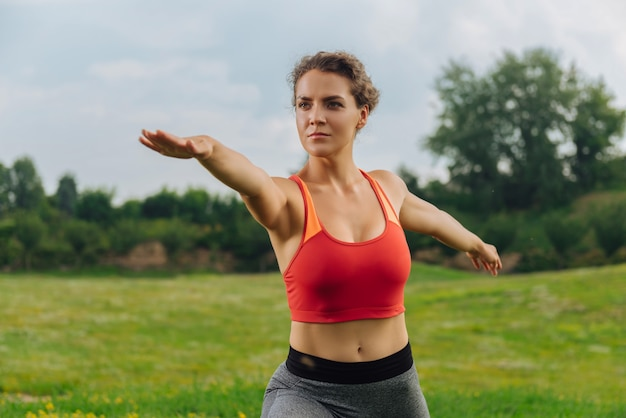 Dunkeläugige lockige frau, die ihren stoffwechsel ankurbelt, während sie im freien sport treibt