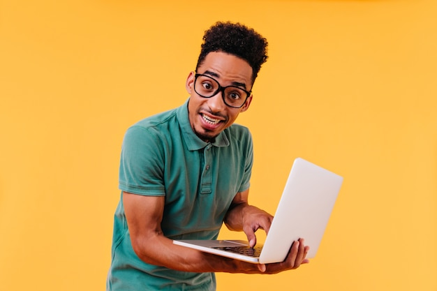 Dunkeläugiger internationaler student, der mit weißem laptop aufwirft. innenfoto des männlichen freiberuflers, der auf tastatur schreibt.