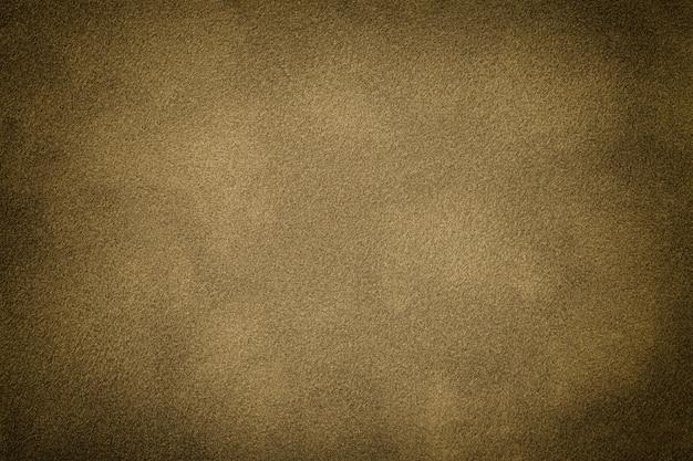 Dunkelbeiger matter hintergrund des wildlederstoffes mit vignette, nahaufnahme. samttextur des nahtlosen braunen textils mit farbverlauf, makro.