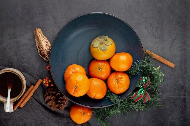 Dunkelblaue platte mit persimone und mandarinen