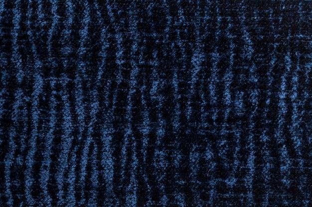 Dunkelblauer flaumiger hintergrund des weichen, flaumigen stoffes, beschaffenheit der textilnahaufnahme