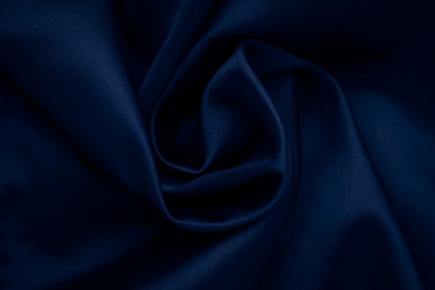 Dunkelblauer gewellter seidenhintergrund. abstrakte stoffoberfläche, textil aus stoff. tapete aus satin, zerknitterte textur des materials.