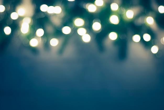 Dunkelblauer grüner verschwommener weihnachtshintergrund mit bokeh-girlandenlichtern und unscharfer fichtenzweiggrenze