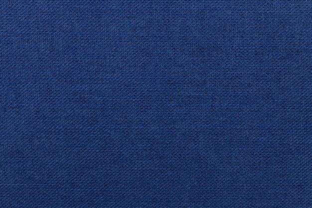 Dunkelblauer hintergrund vom textilmaterial. stoff mit natürlicher textur.