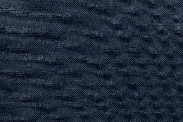Dunkelblauer hintergrund von einem textilmaterial. stoff mit natürlicher textur. hintergrund.