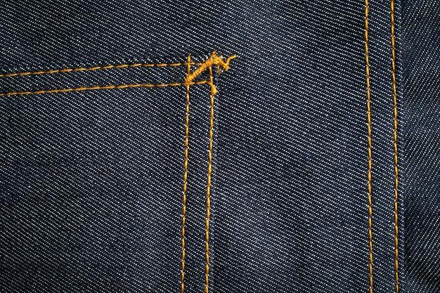 Dunkelblauer jeansbeschaffenheitshintergrund mit tasche.