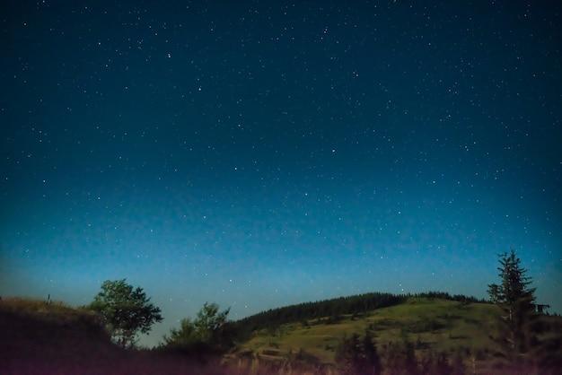 Dunkelblauer nachthimmel mit einem baum und vielen sternen, galaxiehintergrund