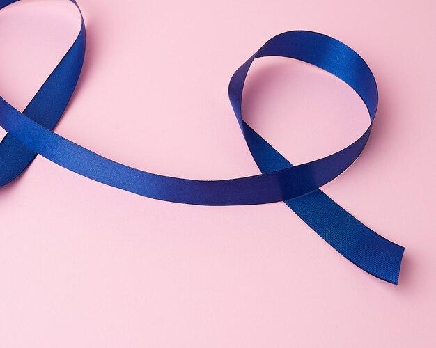Dunkelblaues seidenband verdreht zu schleifen auf einem rosa hintergrund