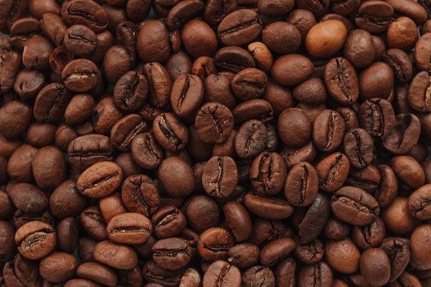 Dunkelbraune geröstete kaffeebohnenhintergrund-draufsicht