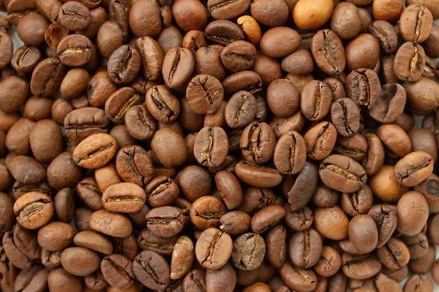 Dunkelbraune geröstete kaffeebohnenhintergrund-draufsichtbeschaffenheit