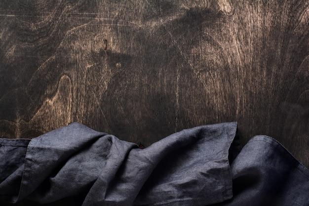 Dunkelbraune holzstruktur mit küchen-serviette oder handtuch aus baumwolle