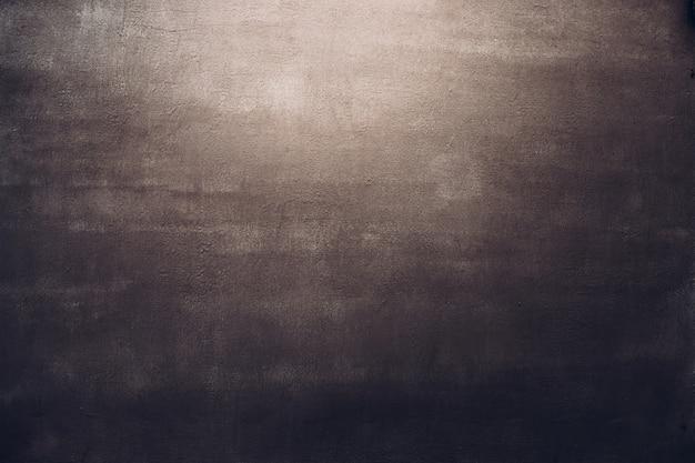 Dunkelbrauner betonwandbeschaffenheitshintergrund im lichtfleck