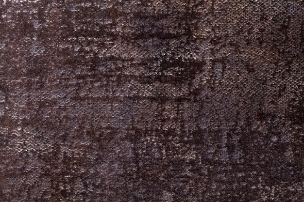 Dunkelbrauner flauschiger hintergrund aus weichem, flauschigem stoff. textur des schwarzen textilhintergrundes mit glänzendem muster.