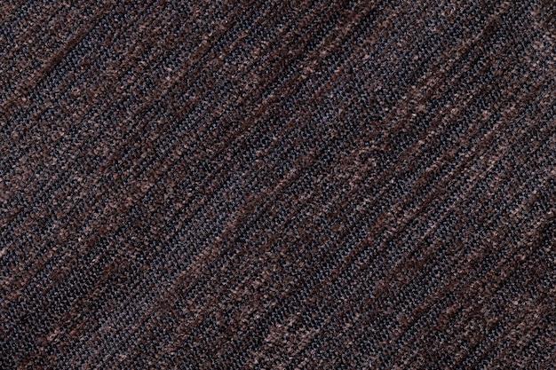 Dunkelbrauner hintergrund eines gestrickten textilmaterials. gewebe mit einer gestreiften beschaffenheitsnahaufnahme.