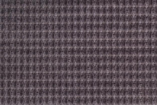 Dunkelbrauner hintergrund vom weichen flaumigen gewebeabschluß oben, beschaffenheit von textilmakro