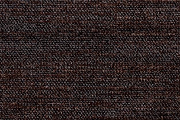 Dunkelbrauner hintergrund vom weichen textilmaterial. stoff mit natürlicher textur.