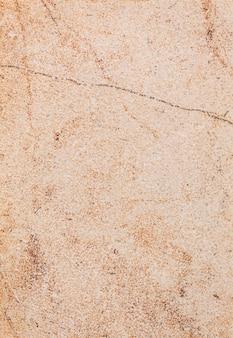 Dunkelgelbe fliese mit abstrakten streifen, strukturiertem rostigem hintergrund, straßenwand in nahaufnahme