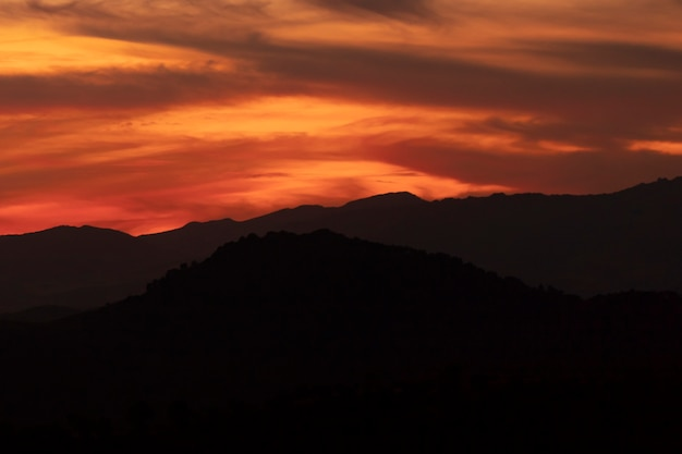 Dunkelgelber bewölkter himmel mit schwarzen bergen