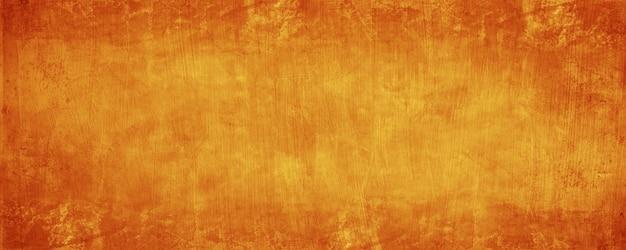 Dunkelgelber und orangefarbener zement und betonwandhintergrund
