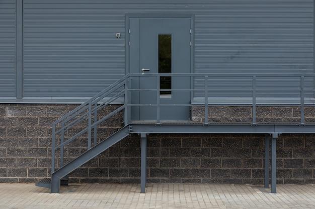 Dunkelgraue hintertür aus metall mit treppe