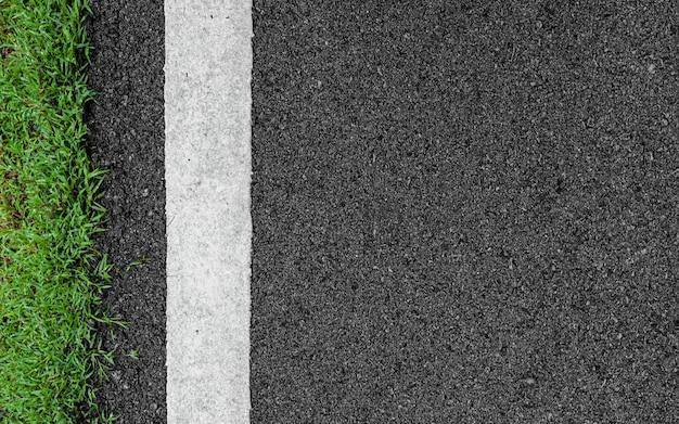 Dunkelgraue straßenstraße des rauen asphaltschwarzen des oberflächenschmutzes und beschaffenheitshintergrund des grünen grases