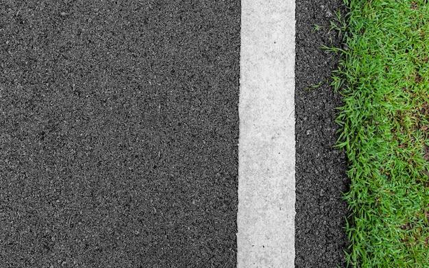 Dunkelgraue straßenstraße des rauen asphaltschwarzen des oberflächenschmutzes und grünes gras