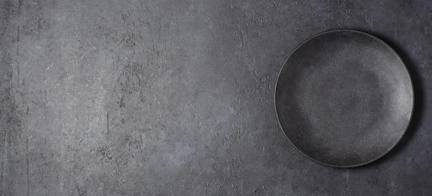 Dunkelgrauer betonhintergrund für entwurf mit schwarzem nahrungsmittelteller. speicherplatz kopieren.