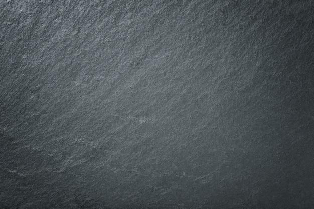 Dunkelgrauer hintergrund des natürlichen schiefers. schwarze steinnahaufnahme der beschaffenheit.