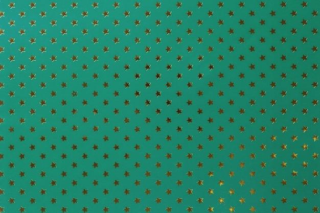 Dunkelgrüner hintergrund vom metallfolienpapier mit einer goldenen sternchen-vereinbarung.