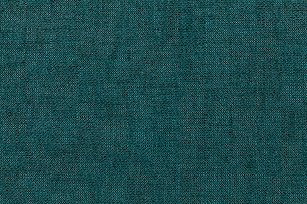 Dunkelgrüner hintergrund von einem textilmaterial.