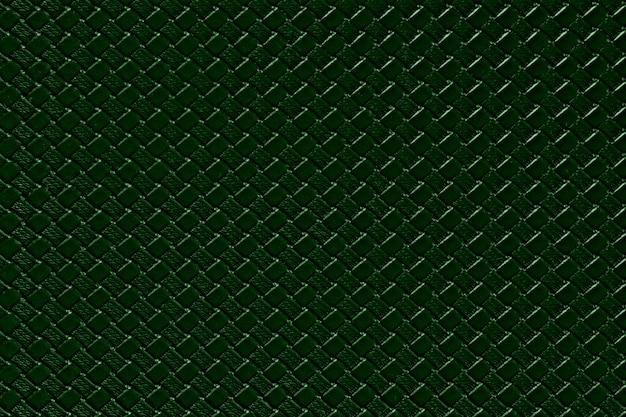 Dunkelgrüner lederner hintergrund mit nachgemachter webartbeschaffenheit. glänzende kunstlederstruktur.