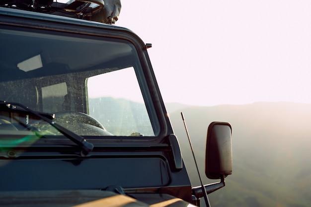 Dunkelgrünes geländewagen in den bergen schließen