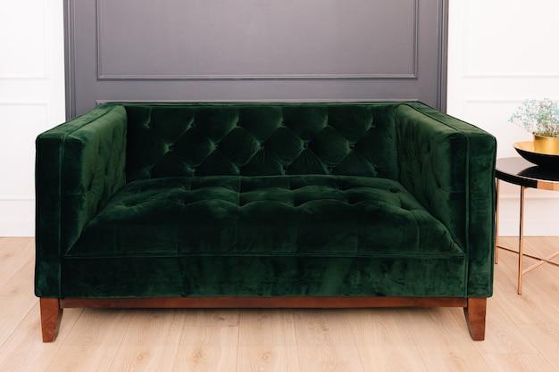 Dunkelgrünes malachit-velours-sofa im innenraum. capitone textil, wildleder, velours, mit knöpfen.