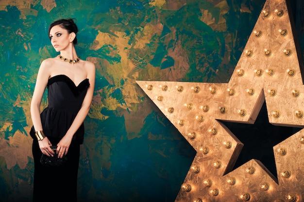 Dunkelhaarige frau im eleganten schwarzen kleid mit clutch-geldbörse im zimmer mit großem dekorationsstern