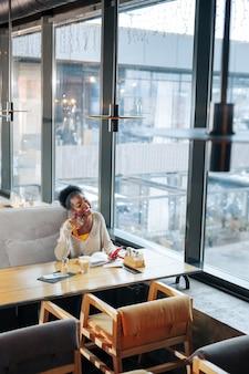 Dunkelhaarige frau. lockige dunkelhaarige frau sitzt auf grauem sofa in einem geräumigen modernen restaurant