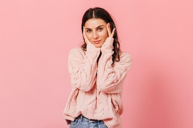 Dunkelhaarige frau mit blauen augen berührt sanft ihr gesicht. mädchen im übergroßen pullover und in den jeans, die kamera auf rosa hintergrund betrachten.