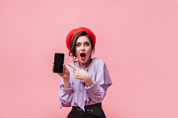 Dunkelhaarige frau mit roten lippen im erstaunen schaut auf kamera und zeigt finger auf schwarzes telefon.