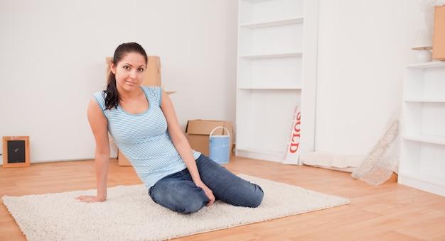 Dunkelhaarige frau sitzplätze auf einem teppich